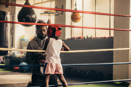 Boxing kid standing inside the ring talking to his trainer