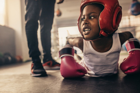 Boxing kid doing push ups on the floor at a boxing gym