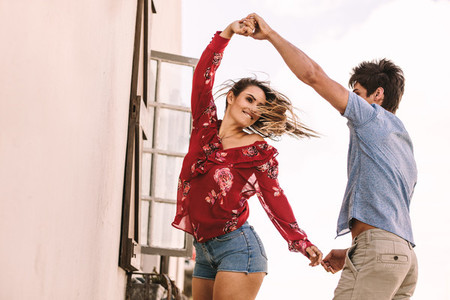 Happy couple dancing holding hands