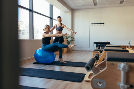 Women practicing pilates workout at a gym