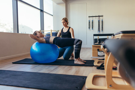 Woman doing pilates workout on a fitness ball at a gym