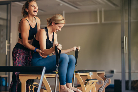 Women laughing while doing pilates workout at a gym