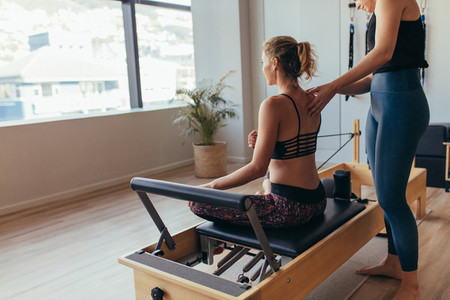 Woman doing pilates workout at the gym with her instructor