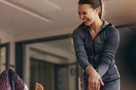 Smiling pilates trainer training woman at the gym