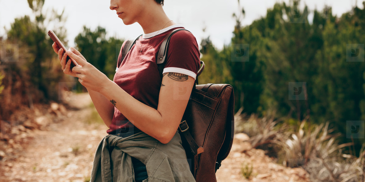 Woman hiker checking her mobile phone