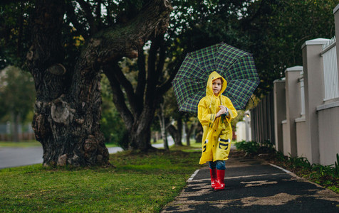 Little girl in raincoat walking with umbrella