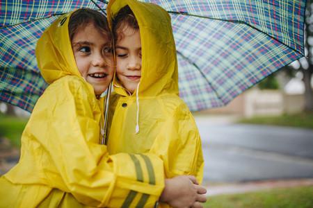 Adorable girls in raincoats hugging each other under umbrella
