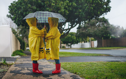 Little sisters in identical raincoats under umbrella