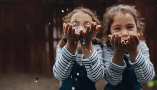 Twin sisters enjoying blowing glitter