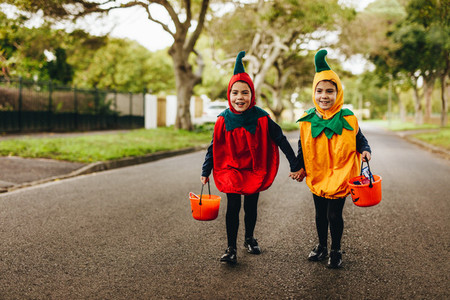 Identical twin girls trick or treating on halloween