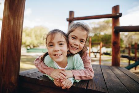 Beautiful little twin girls enjoying at playground