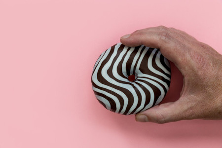 Hand holding striped chocolate donut pink background