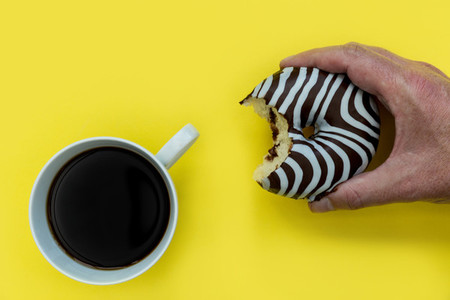 Hand holding striped donut coffee yellow background