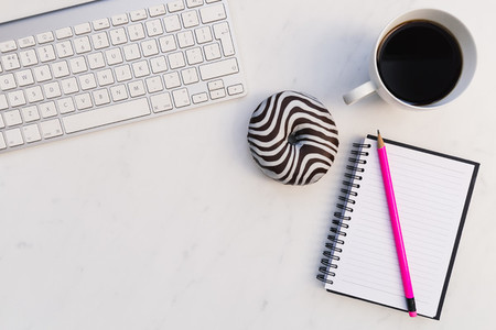 Computer keyboard notebook coffee donut white background