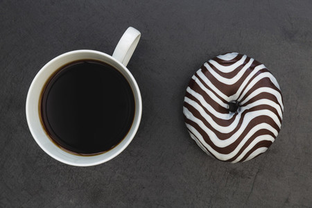 Striped donut and coffee cup dark background