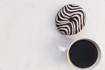 Striped donut and coffee cup white background