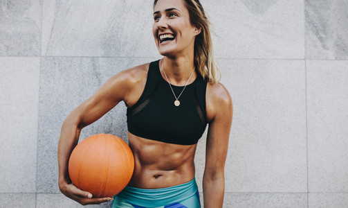 Smiling fitness woman holding a basketball