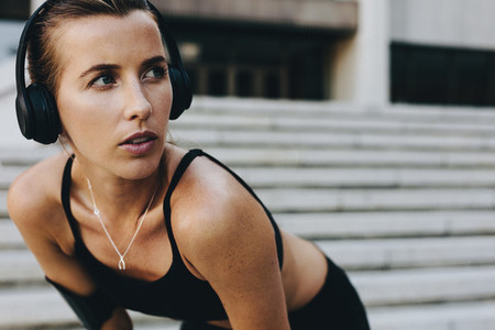 Fitness woman training outdoors listening to music