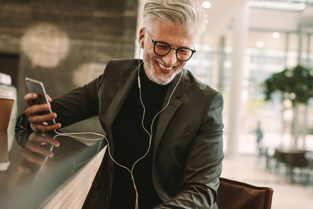Smiling businessman in earphones and cellphone at cafe