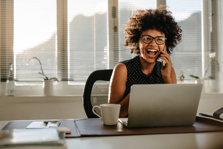 Laughing businesswoman sitting at her work desk