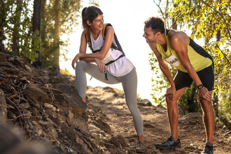 Couple of athletes taking break in mountain race