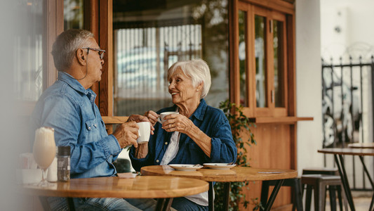 Senior couple talking over a cup of coffee at cafe