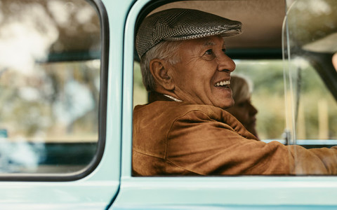 Senior couple traveling in a vintage car