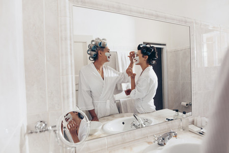 Happy mother and daughter applying face cream standing in the ba