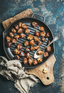 Roasted chestnuts in grilling pan over dark blue background