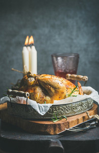 Christmas table set with roasted whole chicken  candles and wine