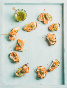 Crostini with smocked salmon  pesto sauce  watercress  capers  Top view