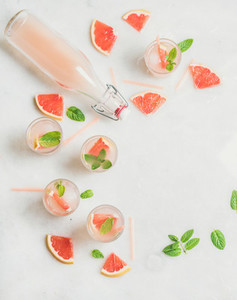 Cold refreshing alcohol cocktail with grapefruit in glasses and bottle