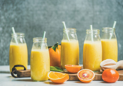 Healthy yellow smoothie in bottles over grey background