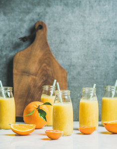 Healthy yellow smoothie with citrus fruit in glass bottles
