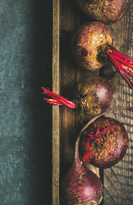 Raw organic purple beetroots in rustic wooden box  copy space