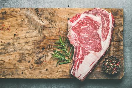 Raw uncooked beef steak rib eye on board  copy space
