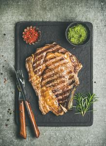 Grilled hot rib eye beef steak on bone with chimichurri sauce