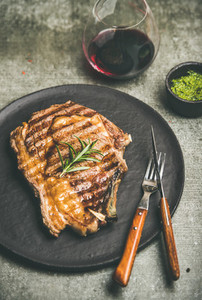 Grilled hot rib eye beef steak with red wine