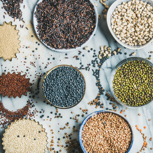 Variety of raw grains  beans  cereals  marble background  square crop
