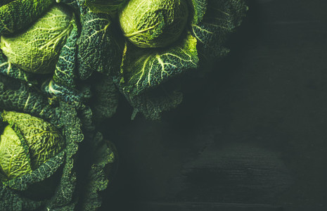 Raw fresh uncooked green cabbage over dark background  copy space