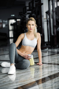 Beautiful athletic girl  poses in the gym with a yellow shaker