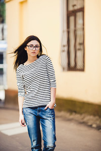 Beautiful model in a striped sweater in glasses