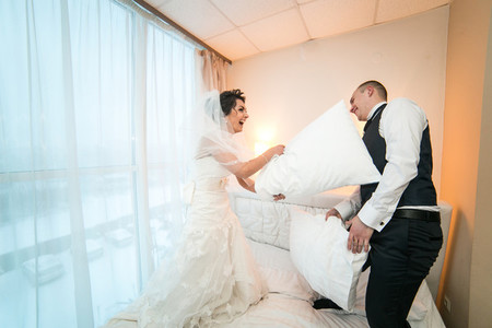 Pillow fight of bride and groom in a hotel room