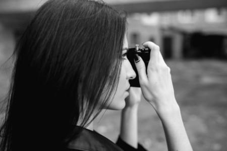 Beautiful female photographer posing with camera