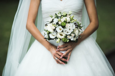 Very beautiful wedding bouquet in hands of the bride