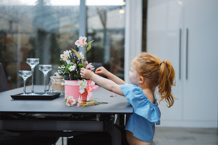 Little girl puts flowers on table