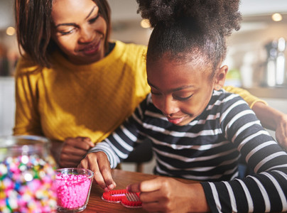 Proud parent watching child use craft beads