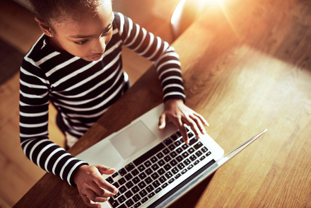 Young ethnic black girl typing on a laptop