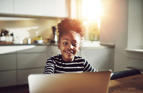 Cute young black girl playing on a laptop
