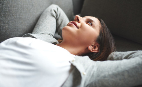 Woman laying on back resting on couch